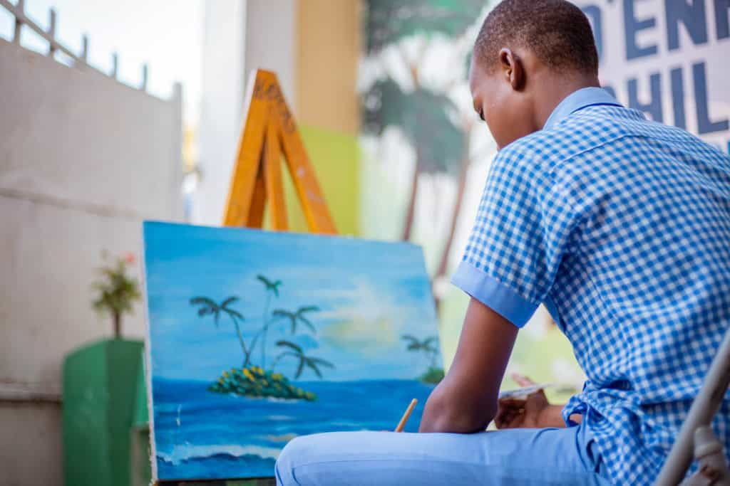 Jetmy is sitting at his project painting a blue sea and sky landscape. Jetmy is wearing his school uniform, blue pants and a blue and white checkered shirt.