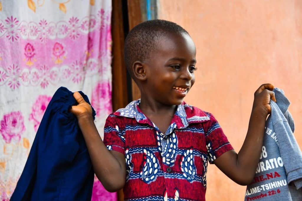 A young boy in Togo holds up a new pair of blue pants and a shirt