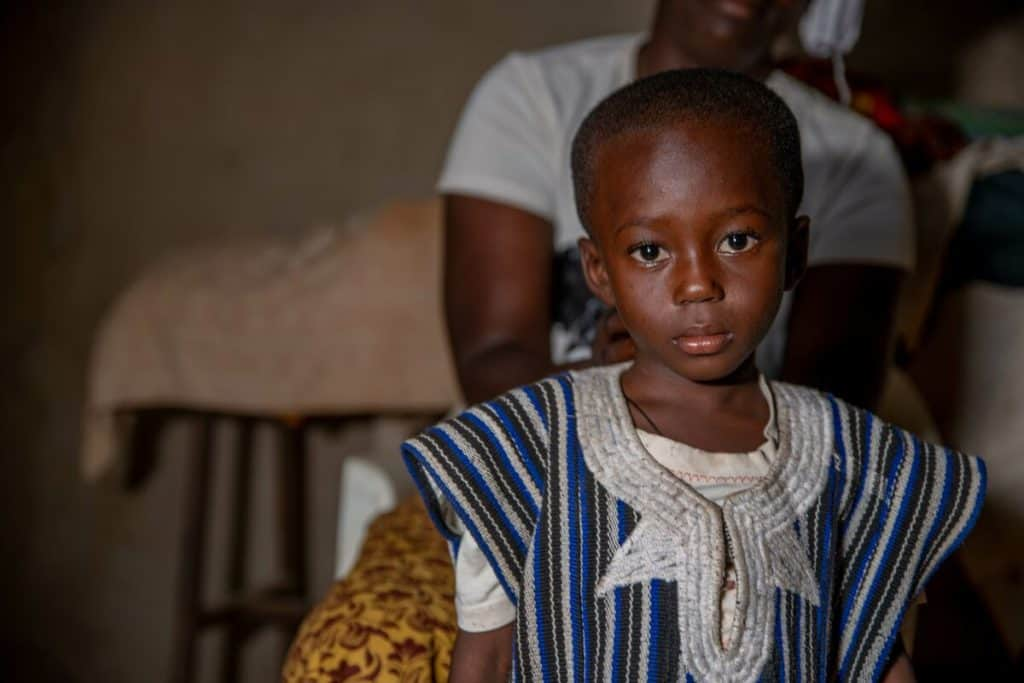 A child in Burkina Faso wearing a somber expression and traditional clothing