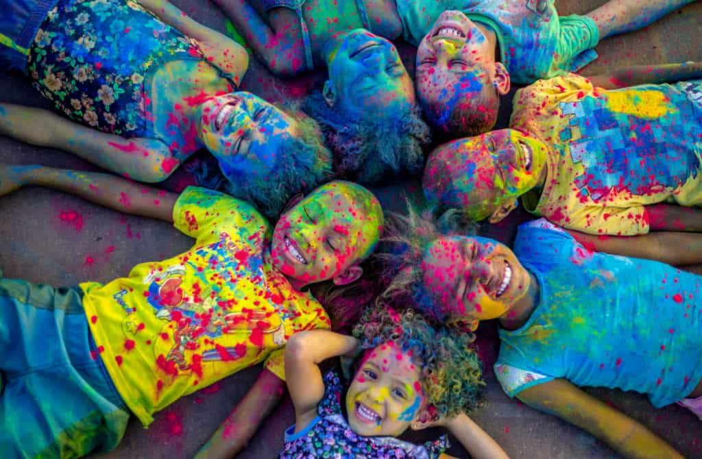 Several children are pictured here, laying in a circle with their heads together. They are covered in colorful powder and are happy and smiling.