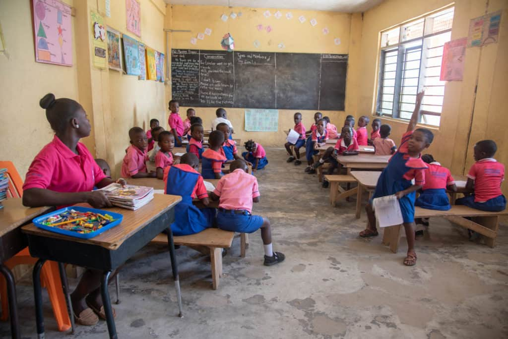 Children, all wearing hot pink and blue uniforms, are in a classroom with yellow walls and a blackboard. The teacher is sitting at a desk holding a set of workbooks.