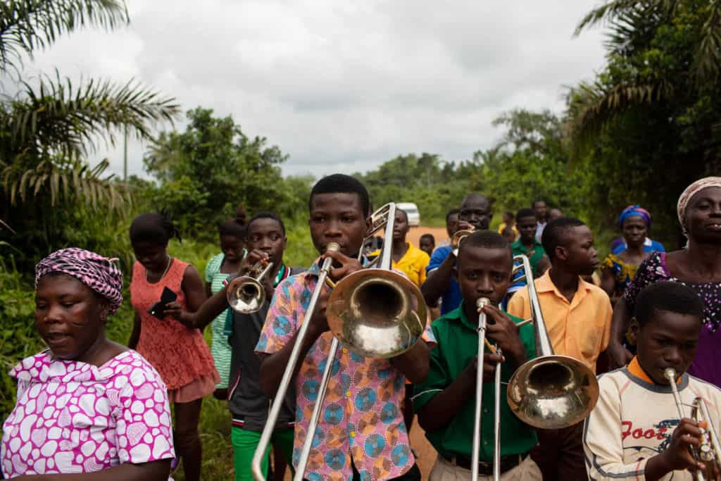 A group of young men are walking down a road bordered by trees playing musical instruments, trombones and trumpets.