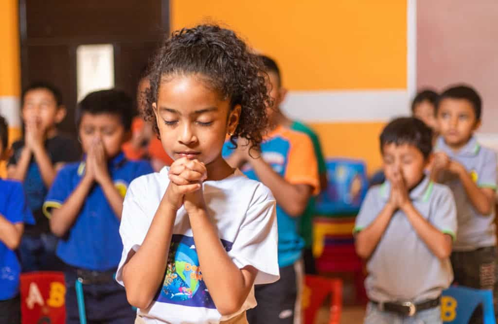 Allison is wearing a white shirt with a design on the front. She is standing in a room with orange walls praying. Her hands are folded in front of her. Other children are behind her praying.
