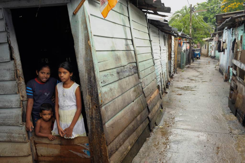 Three Sri Lankan children in a home, with a view from an alley.