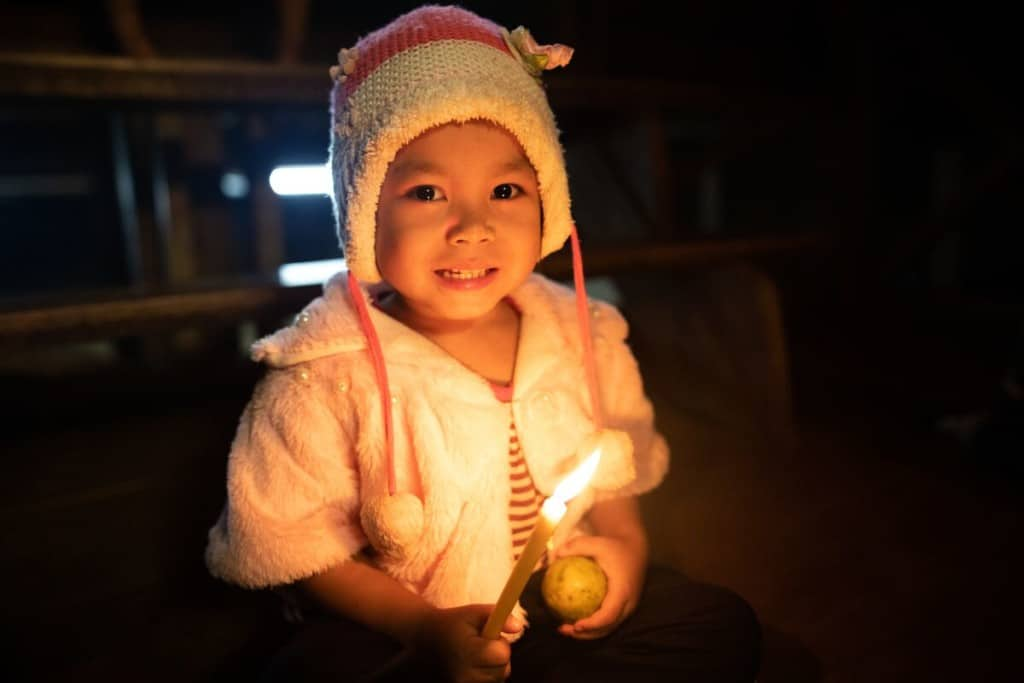 A young child wearing a hat holds a candle in one hand and an orange in the other