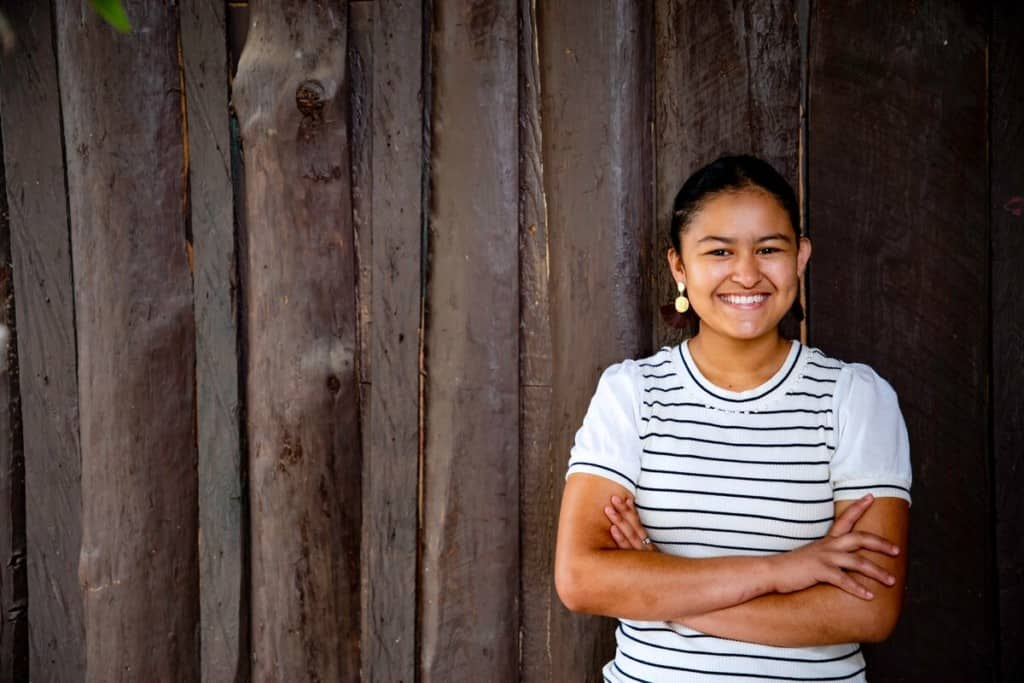 A teen girl in a white and black striped shirt smiles and crosses her arms while standing in front of a wooden fence