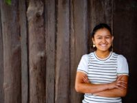 An adolescent woman in a white and black striped shirt smiles and crosses her arms while standing in front of a wooden fence