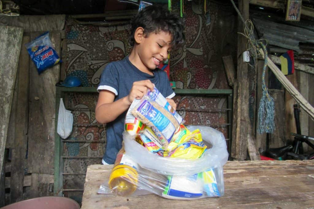 A boy smiles as he looks through a plastic bag filled with food staples