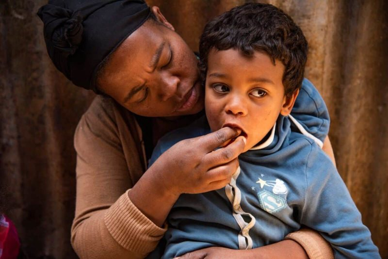 A mother in Ethiopia feeds her 4-year-old son
