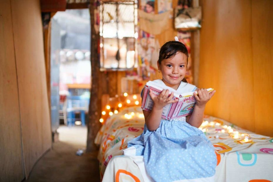 A girl sits on her bed holding an open Bible. There are twinkling lights in the background