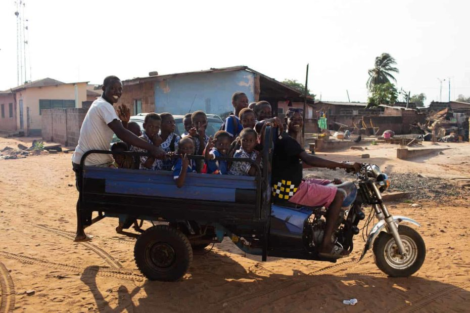A group of boys and a man in a white shirt are riding in a blue motorcycle truck. There are buildings in the background.