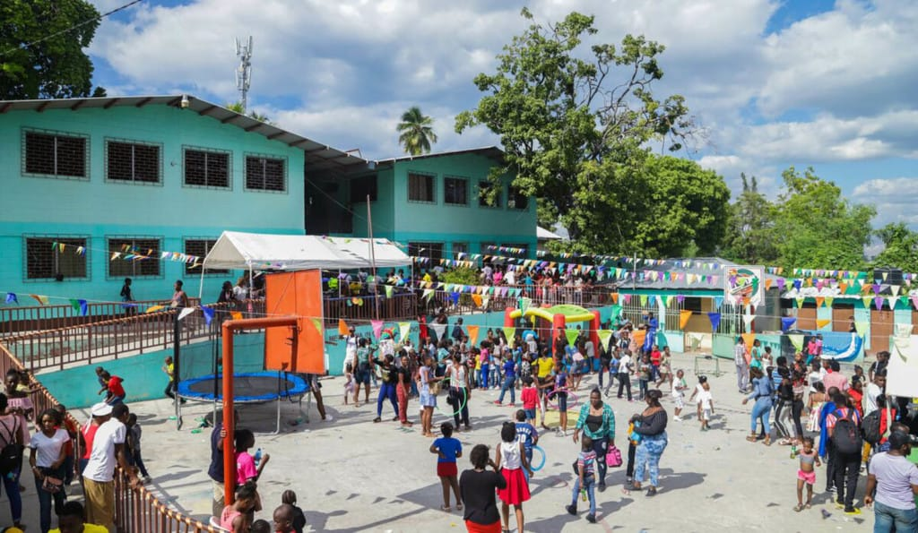 A large group of people participating in the Fun Fair Day at the Compassion project. They are all in the courtyard in front of a green building.