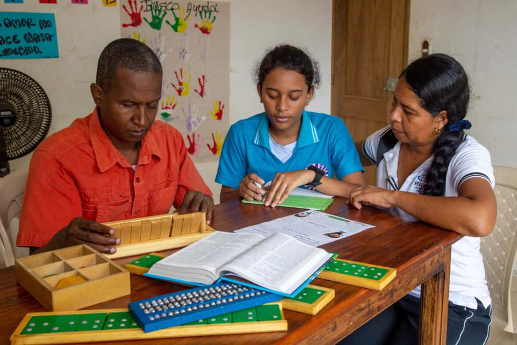 Liseth, wearing a blue shirt, is at the project with her tutor Deysi, wearing a white shirt, and her braille tutor Juan Carlos, wearing a red shirt. Liseth is writing a bible verse in braille.