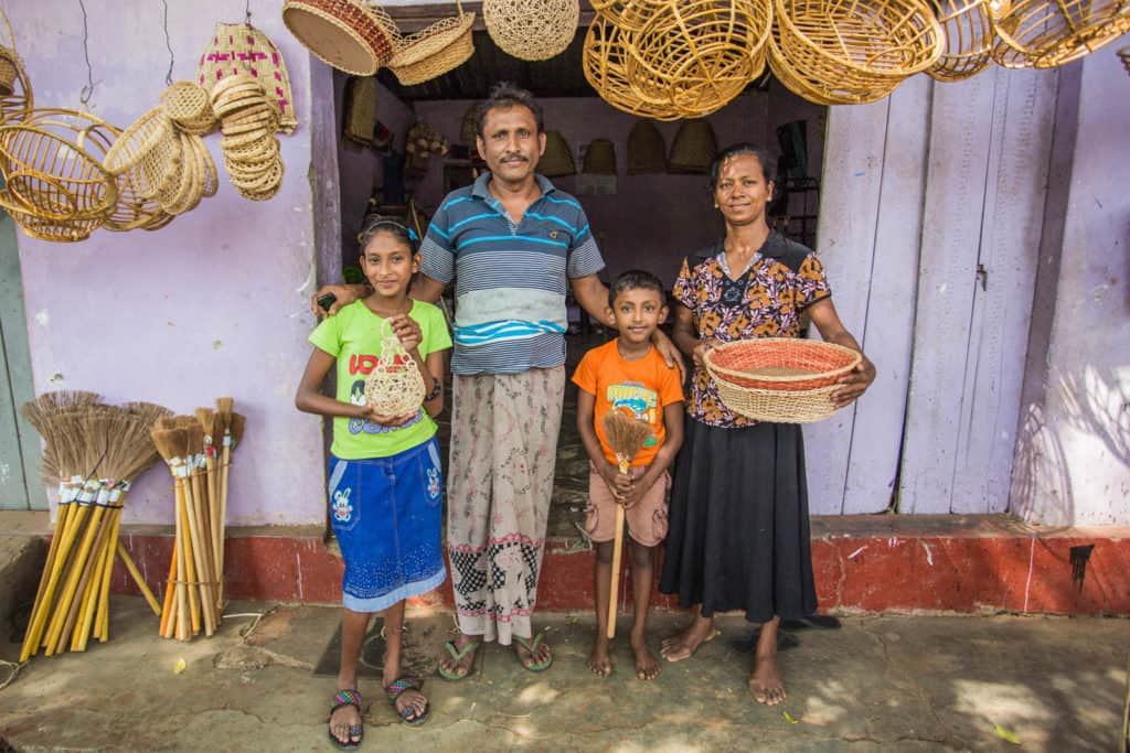 Dilakshi, wearing a blue skirt and a green shirt, is standing with her family in front of their grandmother's home, where they live. There are baskets hanging above them.