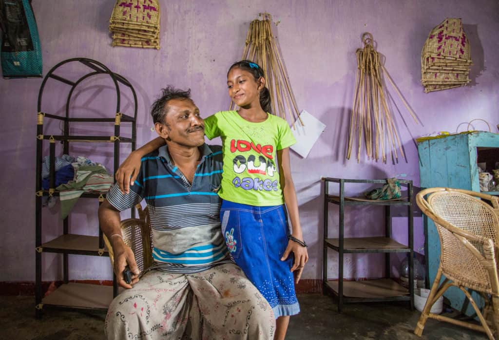 Chamodya Dilakshi, wearing a blue skirt and a green shirt, is with her father, Jayakodi, in his furniture shop that the church helped secure. Jiyakodi is sitting and Chamodya has her arm around him. The wall behind them is purple and there are various pieces of furniture all around them.