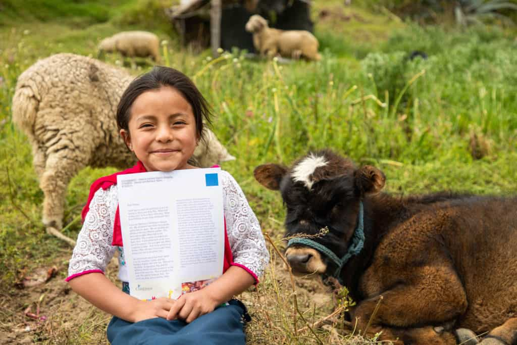 A girl sits in a grassy field with sheep and a cow behind her, holding a letter from her sponsor and smiling