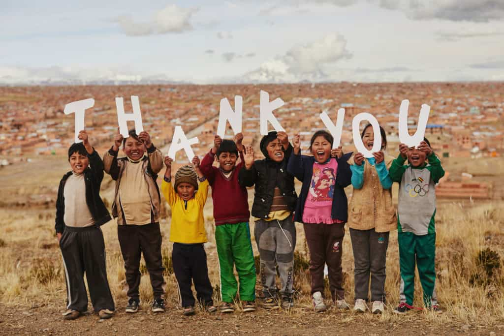 Eight children stand on a hill above a city holding up white letters that say THANK YOU.
