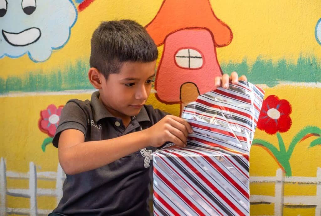 A boy wearing a gray shirt sits in front of a colorfully painted wall, opening a square Christmas gift wrapped in shiny paper.