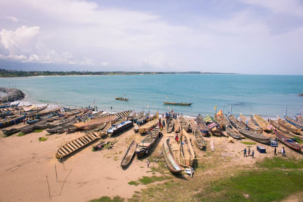 Many wooden boats on the shore of a large body of water