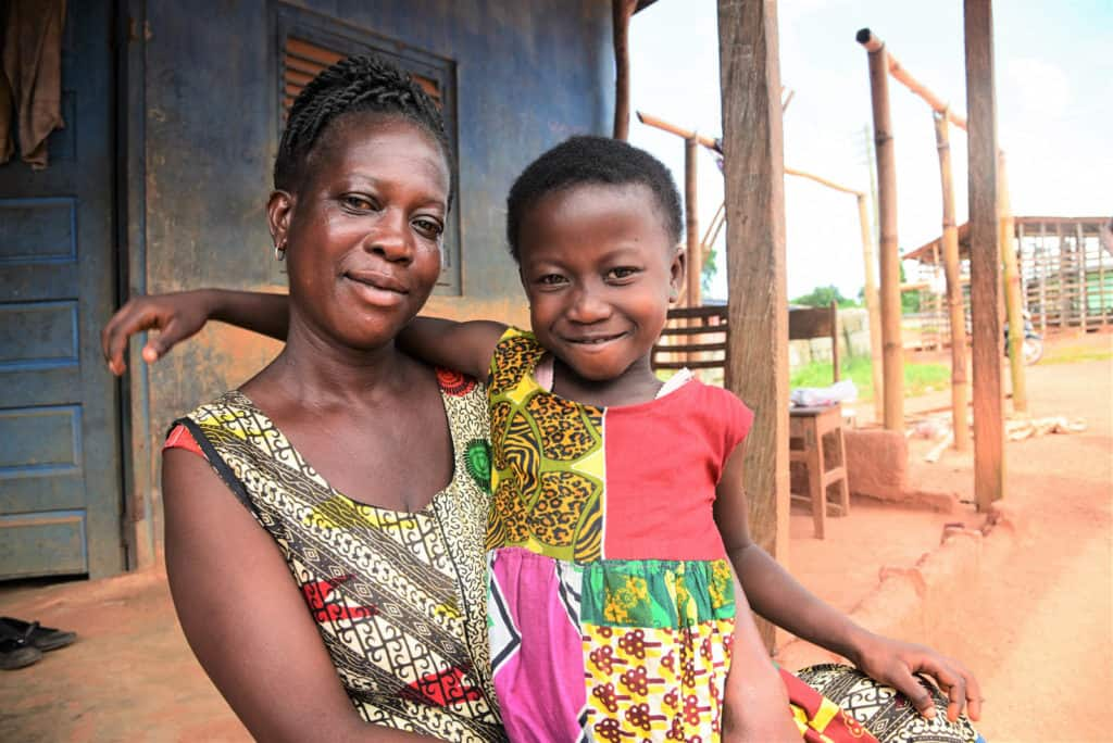 Sabina and her mother are both looking at the camera and smiling, wearing colorful shirts. The background is a blue building. Sabina has her arm around her mother.