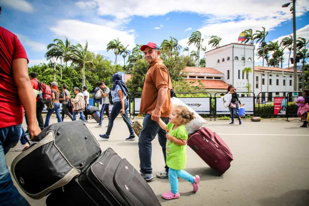 An older man holding the hand of a little girl while pulling a suitcase.