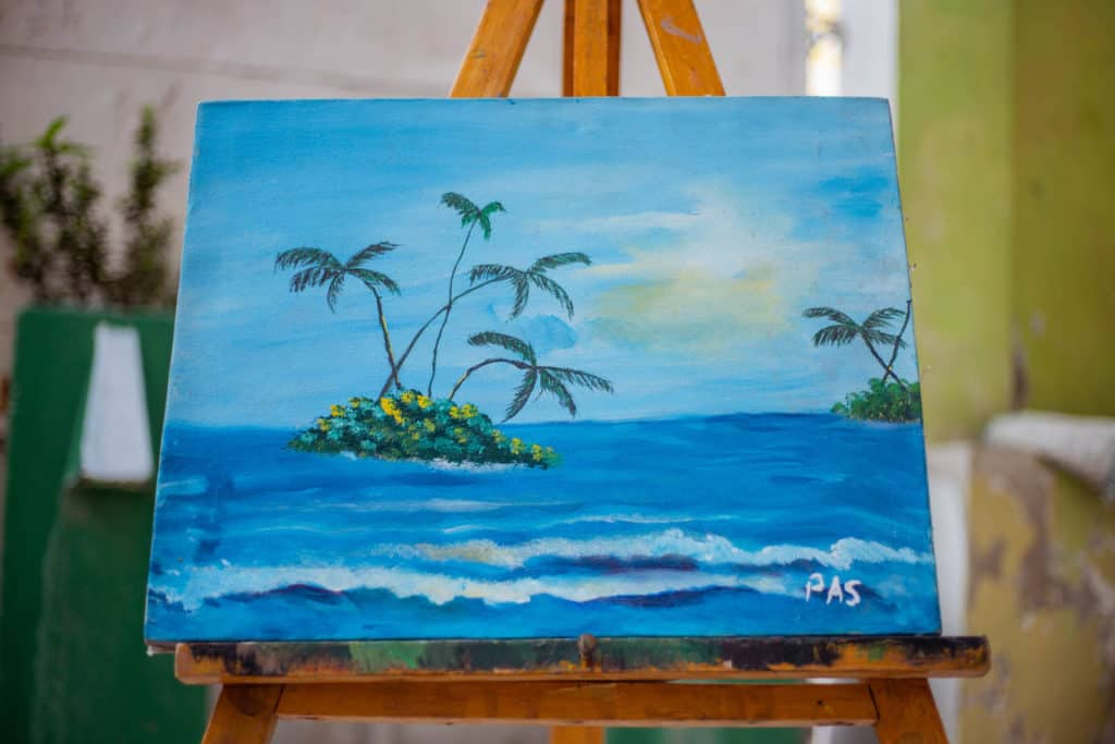 Jetmy's painting. The painting is of a blue sea and sky, with palm trees in the sea.