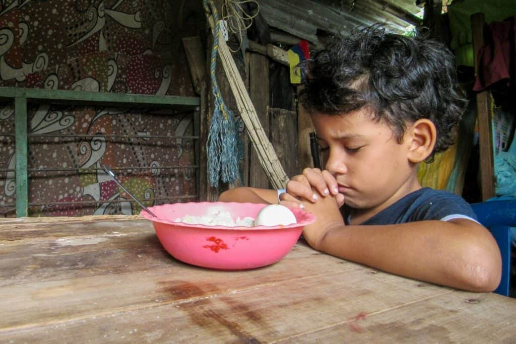 A young boy in Colombia closes his eyes and folds his hands in prayer before a meal. There is a pink bowl with food in it on a table in front of him.