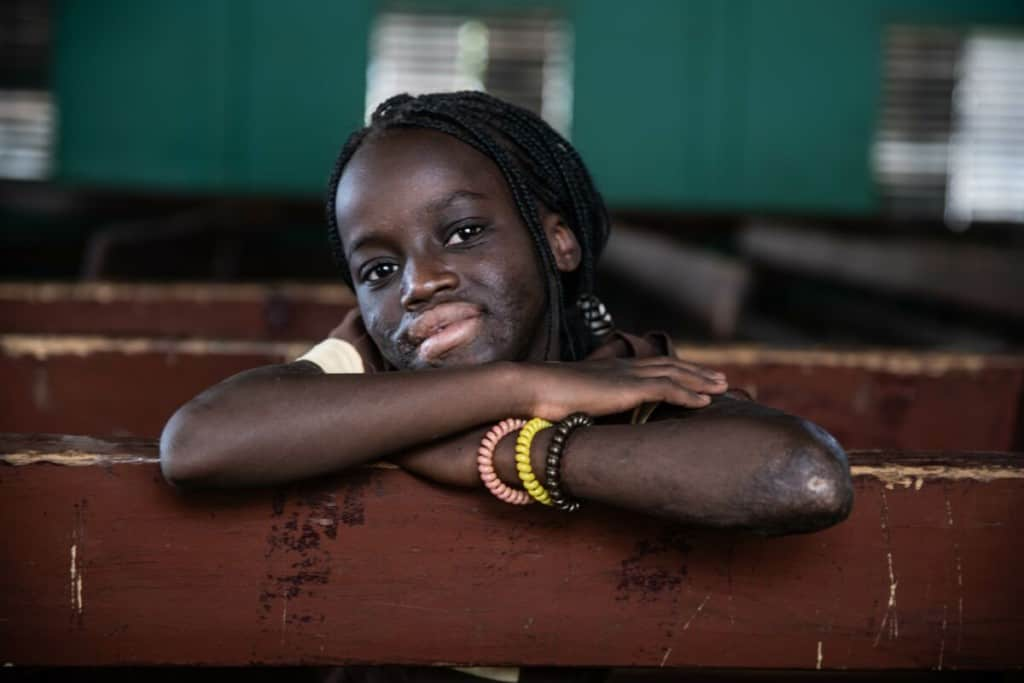 A girl rests her arms and head on a wooden bench and smiles. She is wearing three bracelets.
