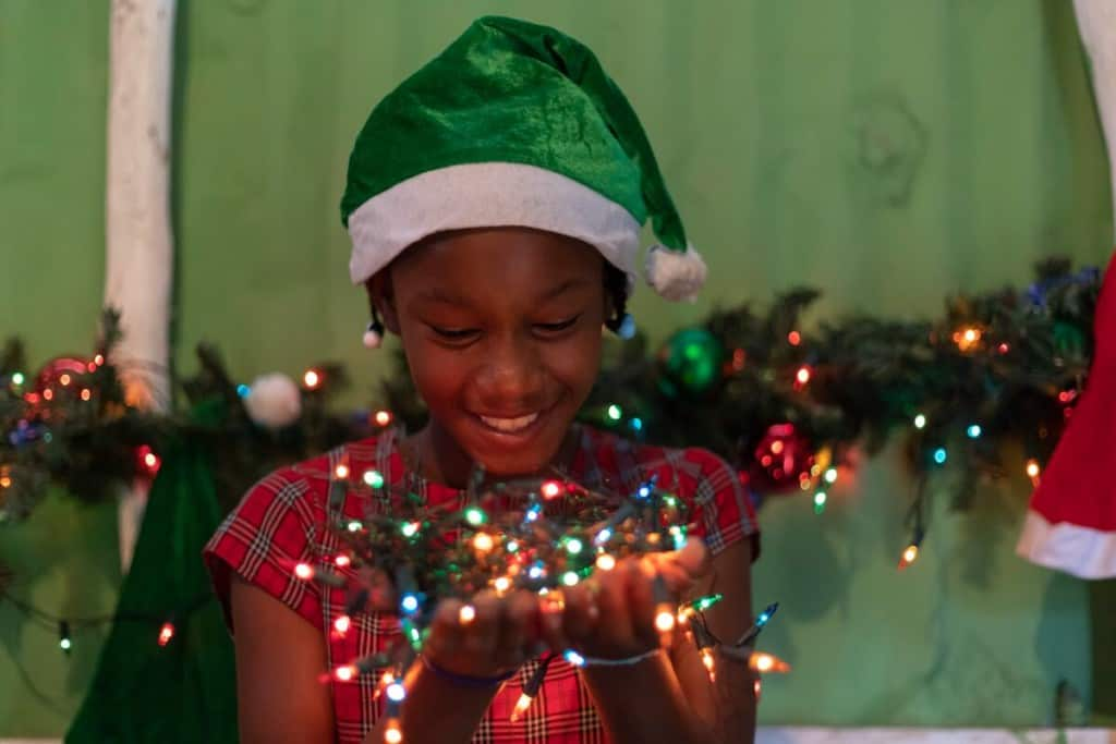 An adolescent girl wearing a green Santa hat and plaid red dress holds a bundle of colorful Christmas lights