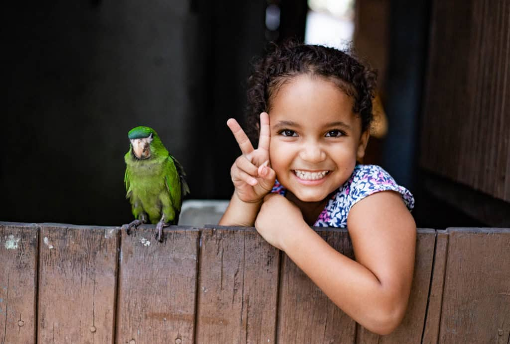 Maisa is at the back door to her house posing with her aunt's green parrot, Tico.