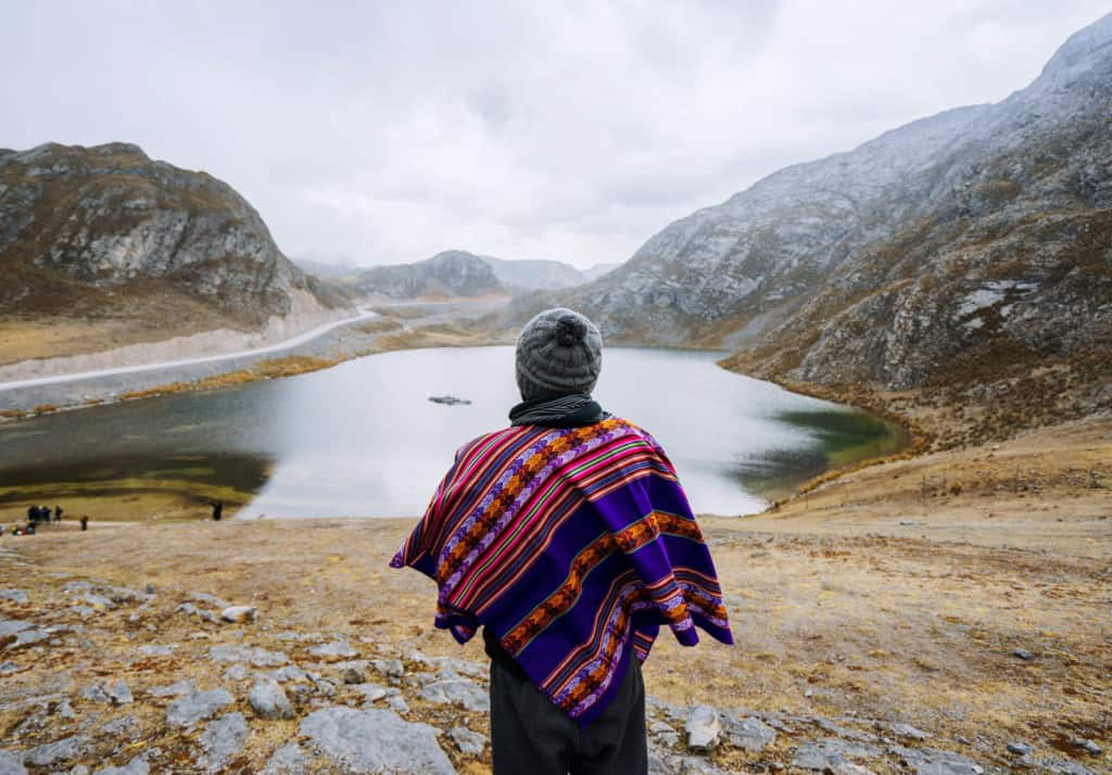 Person standing looking at lake in a mountain valley.