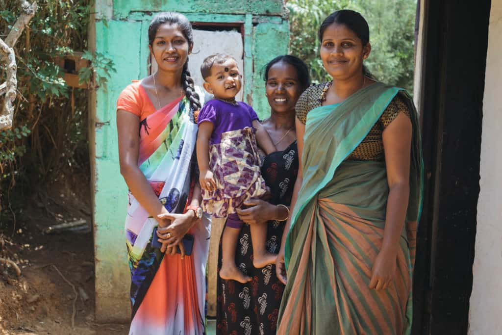 Pavishana is wearing a dress with a purple bodice and a yellow and purple floral print skirt. Her mother, Malathy, wearing a black dress with red and white designs on it, is holding her. They are standing with Pramila, her Project Implementer, and Angel, the Project Manager. All of the women are outside Malathy's home.