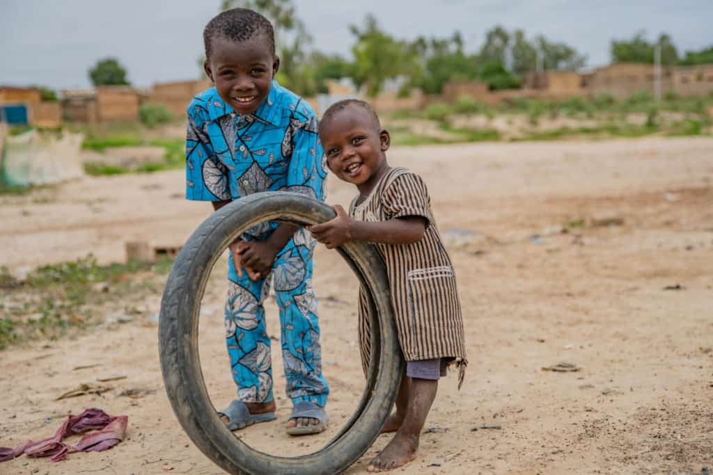 Samsoudine is wearing a blue outfit with black and white designs on it. He is standing outside his home with his younger brother, Adboul, who is holding up an old tire.