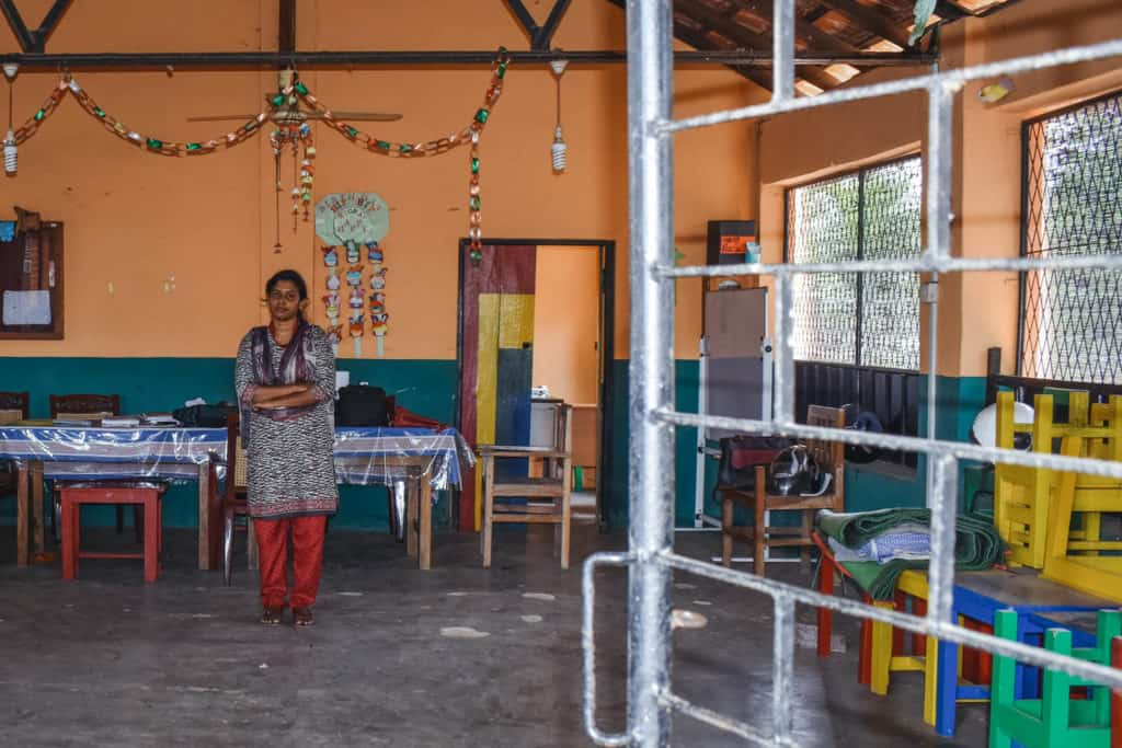 Joanna is wearing red pants with a black and white shirt. She is standing inside the empty Compassion center with her arms crossed in front of her. There is a long table behind her and there are colorful rings of paper hanging above her.