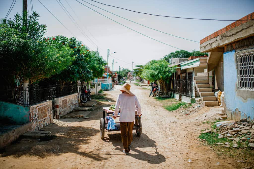 A person in a white shirt and a straw hat is pushing a cart down a dirt and gravel road.
