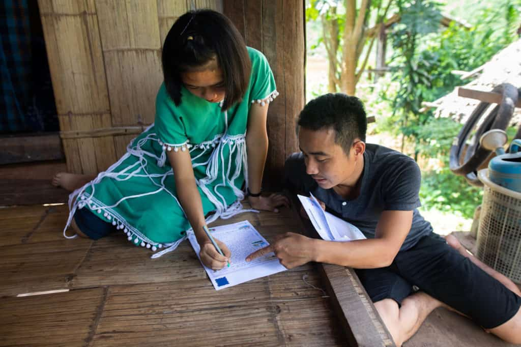 A Compassion staff member in Thailand helps a girl wearing a green and white dress to write a letter.