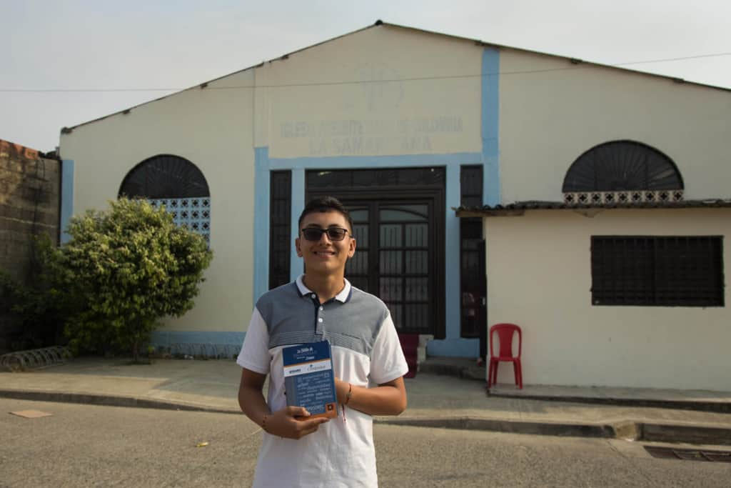 Julian, in a gray and white shirt and sun glasses, is holding the blue Bible he received at the project during a special event. He is standing in front of the church, which is pale yellow and has a black door and blue trim.