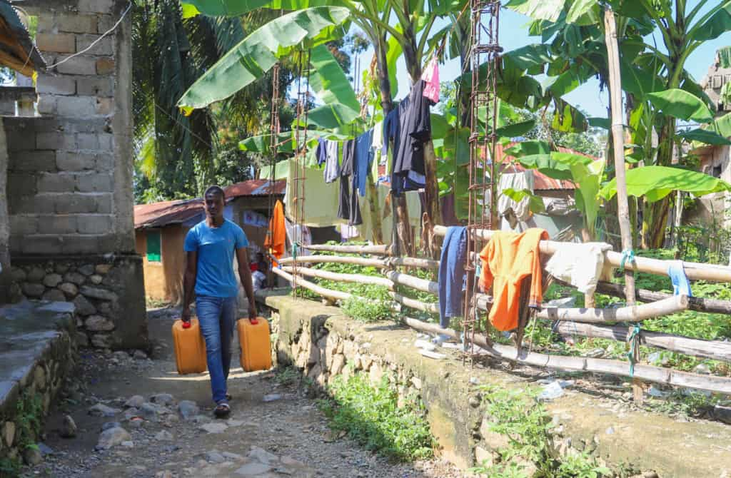 Young man wearing a blue shirt and jeans. He is carrying two large yellow containers full of water home for his family. There are clothes hanging on a clothesline next to him.