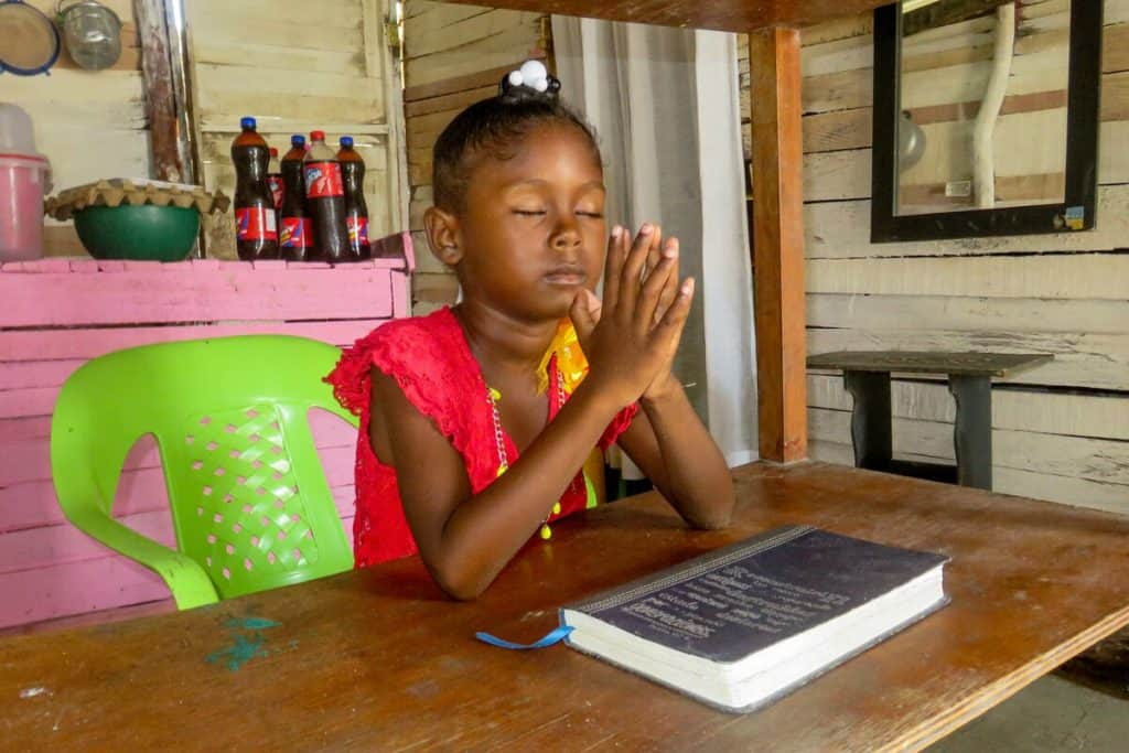 A girl sitting in a green plastic chair closes her eyes and presses her hands together in prayer. She is sitting in her new home at a table, where a Bible sits in front of her.