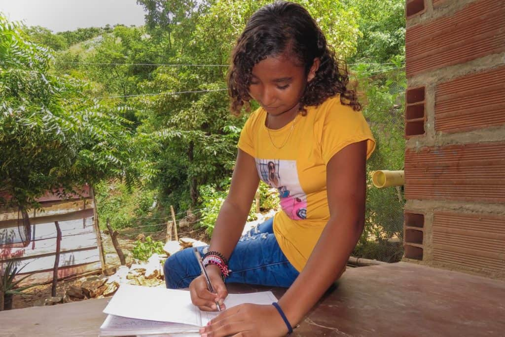 Rosa is wearing jeans and a yellow shirt. She is sitting outside her home and is doing the activities in her education guide from school.