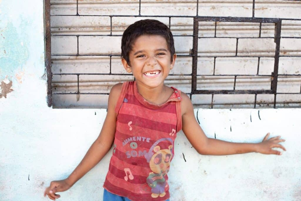 A Brazilian child wearing a red shirt smiles in front of a wall.