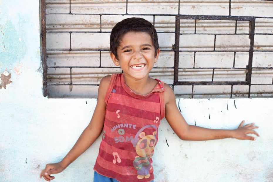 A Brazilian child wearing a red shirt smiles and stands in front of a wall