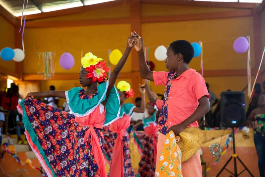 Students from the dance team in the gym, performing in the Christmas Show. They are wearing traditional outfits as they dance.