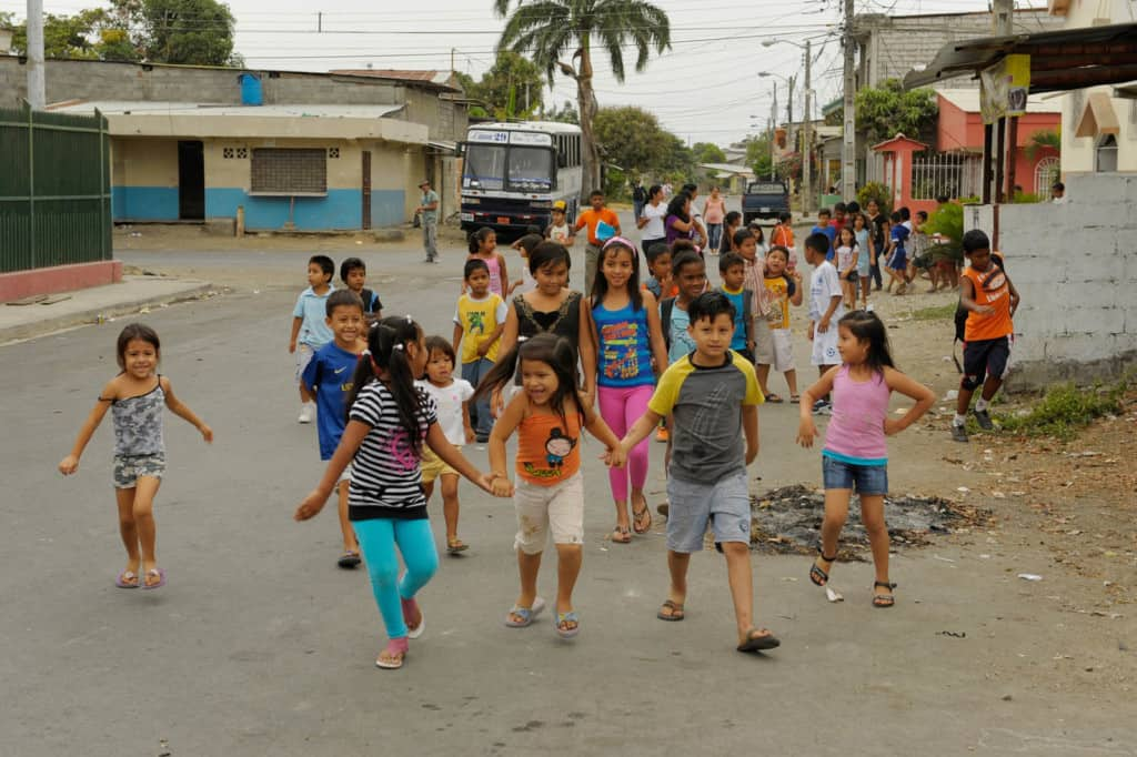 Young boys and girls walk smiling and laughing, some holding hands together, as they stroll as a large group on a paved street in their neighborhood in Ecuador. A bus is no the road behind them near various buildings on either side of the street.