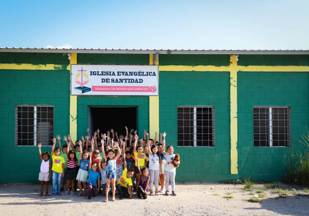 Classmates standing in front of the church. It is a green building with yellow accents. The children are all raising their hands.