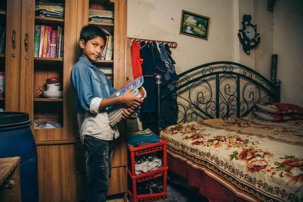 Boy wearing a denim shirt and jeans. He is standing in his room and behind him is a large cabinet full of his older siblings' books. He is holding an armful of books and next to him is his bed.