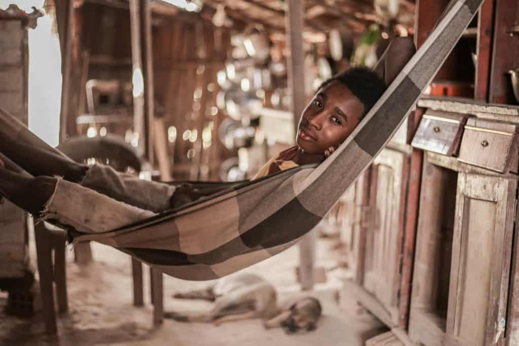 A boy lays in the hammock where he sleeps every night. The house where he and his family live has just one bedroom, so João and his brother sleep in the living room.