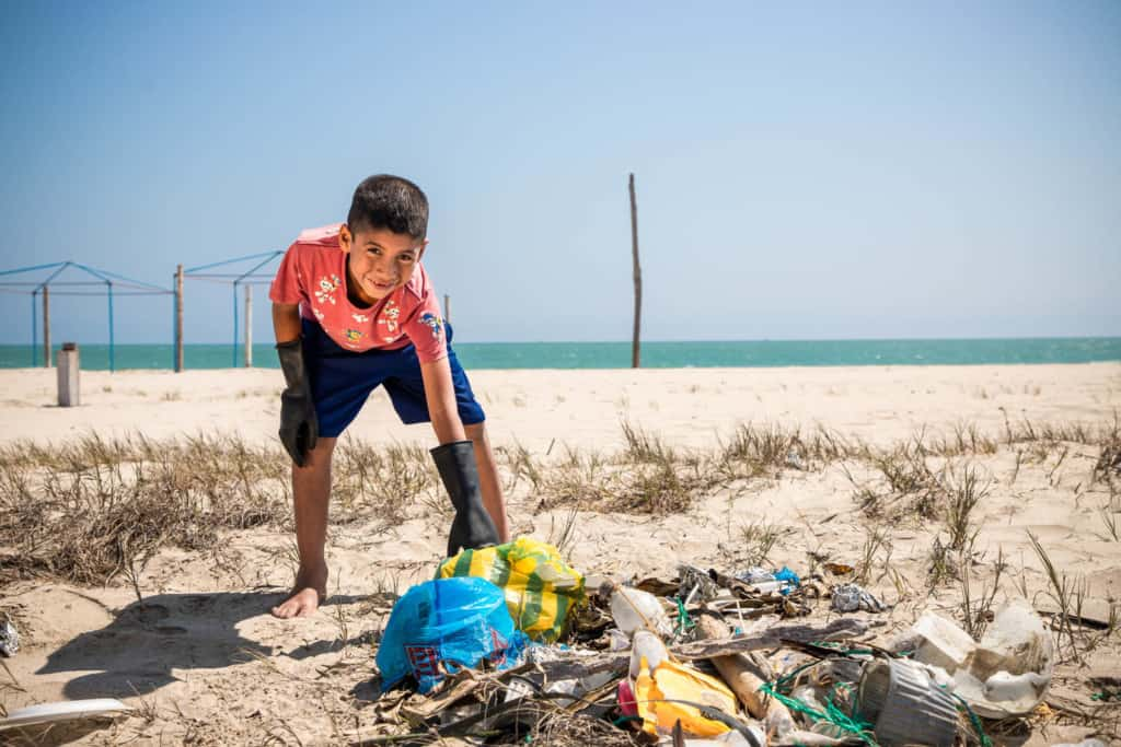 Boy wearing black shorts and a red shirt. He is leaning over and picking up trash.