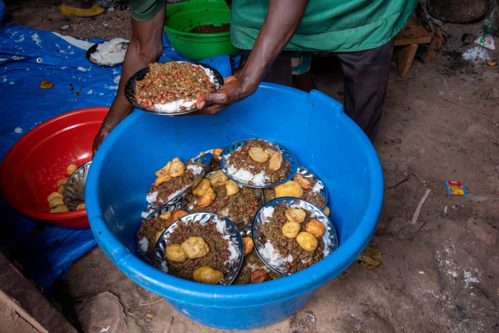 A social worker puts food onto plates before distributing it to the children. The food is rice and beans prepared with greens and Irish potatoes.