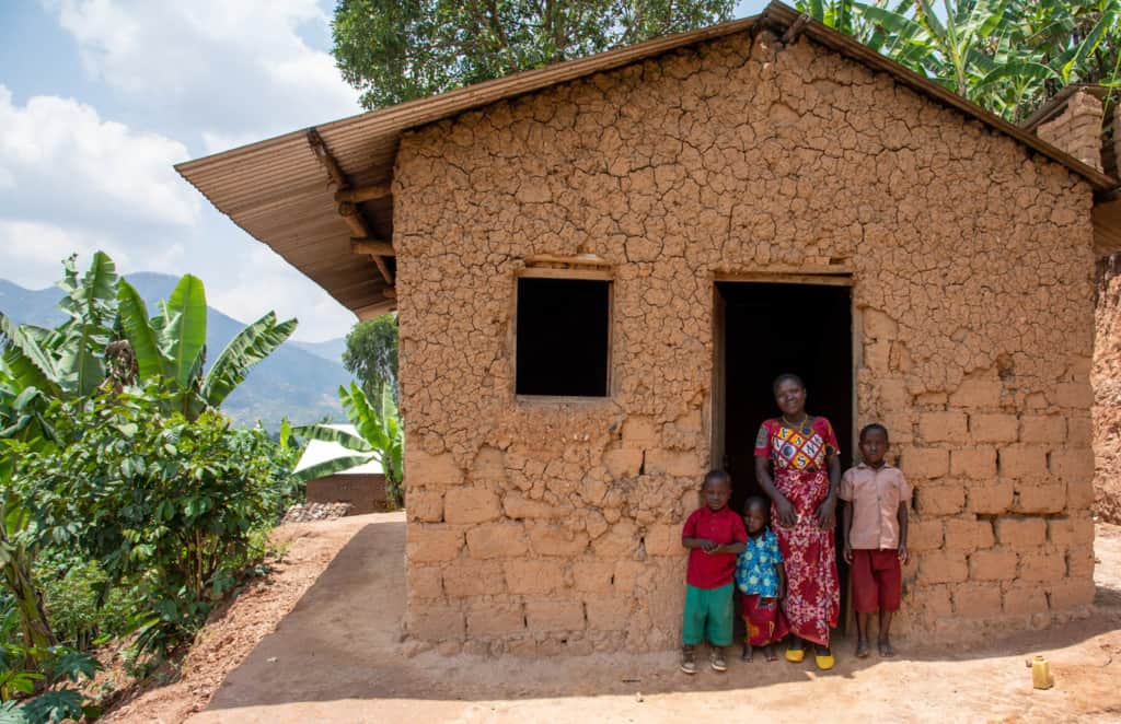 Janvier (in a red shirt and green shorts) is standing at the entrance to his mud home with with his mother and his siblings.